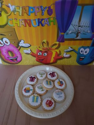 Biscuits with a round icing sheet displaying common Chanuka pictures - menora, draidel and a gift